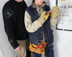 Electrician and apprentice by fusebox